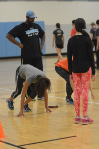 Coach Clifford Wong helps a group of freshman sprinters practice their starts during one of the track team's practices over winter break in the auxiliary gym.