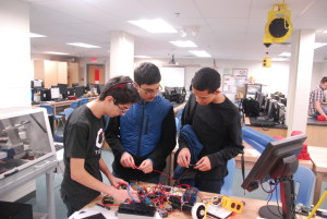 Freshman Kemal Ficici, sophomore Rishabh Jain and freshman Isaac Feldman work on building their robot after school in preparation for competition.