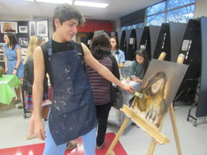 "Junior Reza Mirzaiee paints at the Freshmen Orientation in order to promote the GCM art department. ""I was projecting a medieval rendition of my IB English teacher, Mr. Macindoe onto the canvas,"" Mirzaiee said."