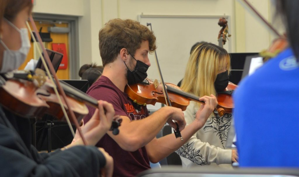 Henry Smith plays the violin at a Marshall choir concert